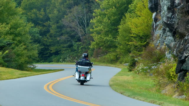 Motorcycle Tourists Riding the Blue Ridge Parkway in North Carolina Tourists on a Motorcycle Riding the Blue Ridge Parkway in the Smoky Mountains near Asheville, North Carolina during the Summer with Rock / Stone Walls and Green Trees Around them. Sound Included. motorcycle stock videos & royalty-free footage