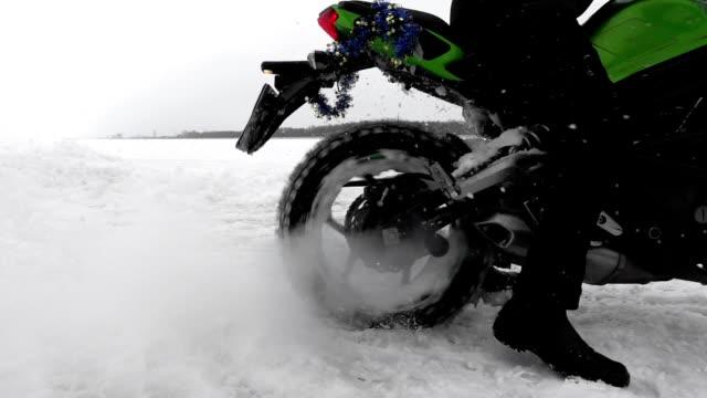 vidéos et rushes de la roue de moto glisse sur la neige coincée dans la congère dans le plan rapproché de motocross. - moto sport