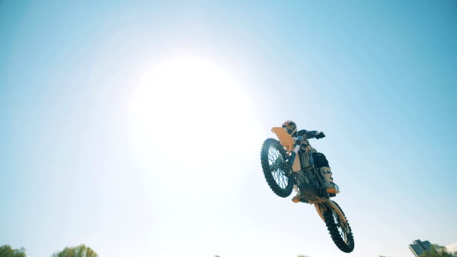 a motorcycler is flying over on his bike after jumping - motocross video stock e b–roll