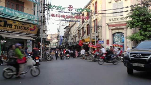 Motorcycles and scooters passing by on the busy streets of Hanoi Vietnam Asia