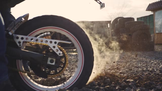 motorcyclist doing tire burnout in the desert, slow motion. professional motorcyclist drift and turns on a motorcycle on the ground, a biker does a trick on a motorcycle - bike tire tracks video stock e b–roll