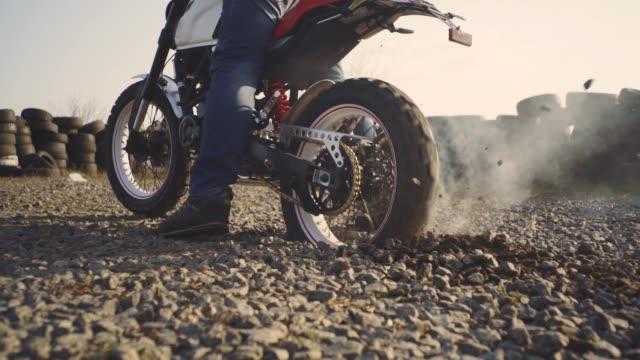 vidéos et rushes de motocycliste faisant l'épuisement des pneus dans le désert, ralenti. motocycliste professionnel dérive et tourne sur une moto sur le terrain, un motard fait un tour sur une moto - moto sport