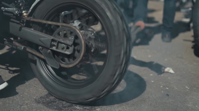 motorcyclist doing tire burnout, slow motion. professional motorcyclist drift and turns on a motorcycle on the asphalt, a biker does a trick on a motorcycle - bike tire tracks video stock e b–roll