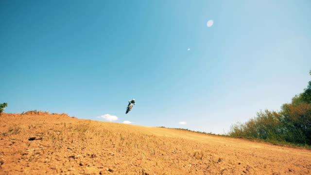 motorradfahrer beendet seinen springtrick - stuntman stock-videos und b-roll-filmmaterial