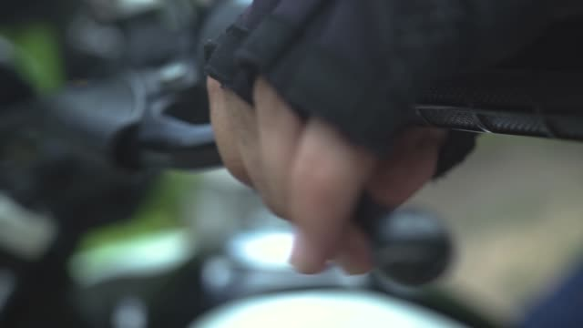 Motorcyclist hands pushing breaks on handlebar close up. Male hands in moto gloves holding breaks on steering wheel Motorcyclist hands pushing breaks on handlebar close up. Male hands in moto gloves holding breaks on steering wheel handle stock videos & royalty-free footage