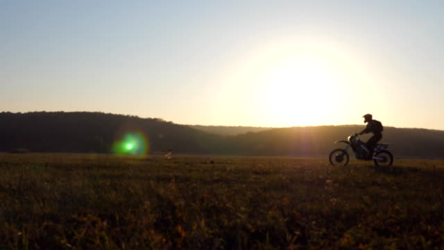 vídeos de stock e filmes b-roll de motorcyclist passing through large field with beautiful sunset at background. warm summer sun lights up green vegetation of field. concept of active rest on nature. slow motion dolly shot - plano charriot