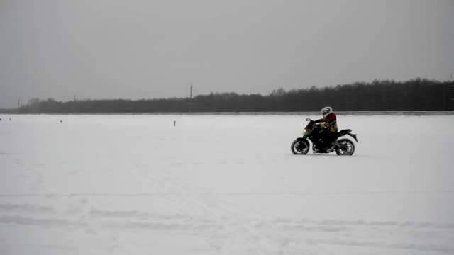 Motorcyclist professional sportsman rides on winter track in snow, side view.