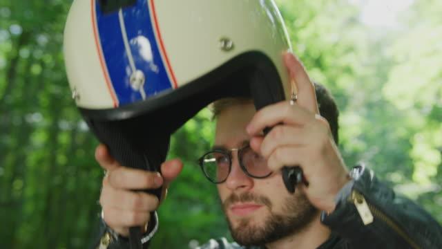vídeos de stock e filmes b-roll de motorcyclist putting on his helmet - helmet motorbike