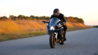 istock Motorcyclist racing his motorcycle on autumn country road. Young man in helmet riding fast on modern sport motorbike at highway. Guy driving bike during trip. Concept of freedom. Front view Close up 1223195673