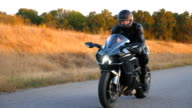 istock Motorcyclist racing his motorcycle on autumn country road. Young man in helmet riding fast on modern sport motorbike at highway. Guy driving bike during trip. Concept of freedom. Front view Close up 1223208248