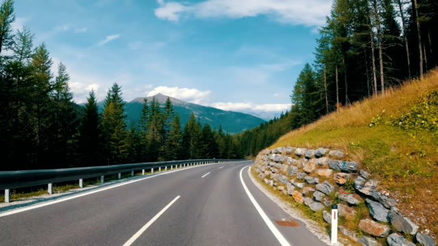 Motorcyclist Rides on a Beautiful Landscape Mountain Road in Austria. First-person view