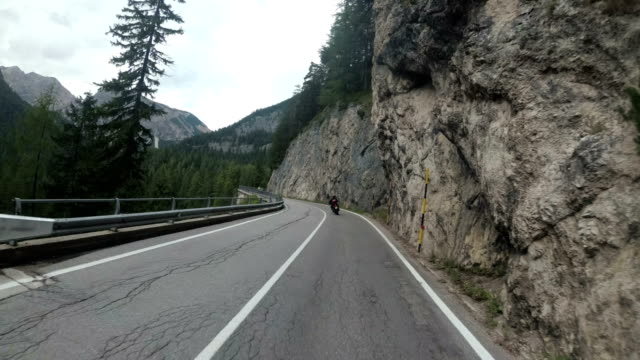 Motorcyclist Rides on a Beautiful Landscape Mountain Road in Italy. First person view