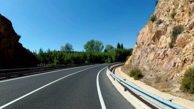 motorcyclist rides on landscape mountain desert scenic and empty mountain road in spain. first-person view - andare giù video stock e b–roll