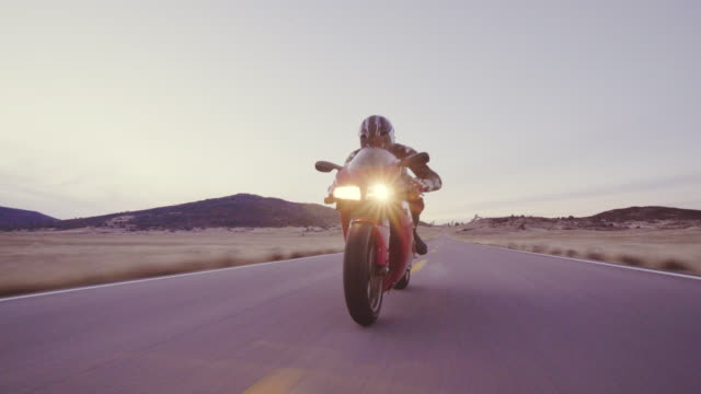 Motorcyclist riding his motorcycle down straight country road going a high speed  at sunset
