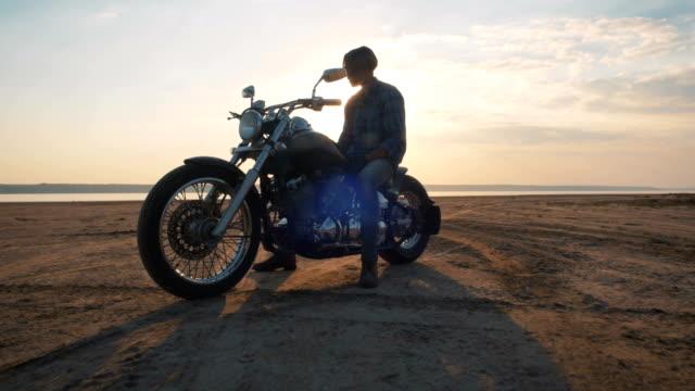 Motorradfahrer, die sitzen auf seinem Motorrad auf der Straße nahe dem Meer bei Sonnenuntergang – Video