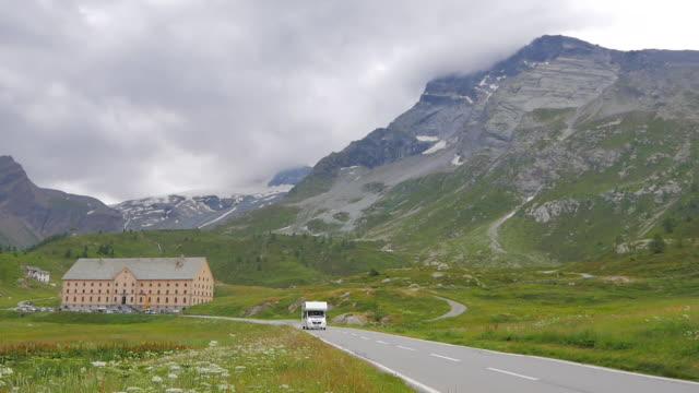 stockvideo's en b-roll-footage met camper driving swiss mountain road - caravan