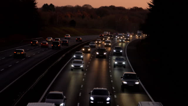 Motorway traffic driving at dusk, cars with headlights.