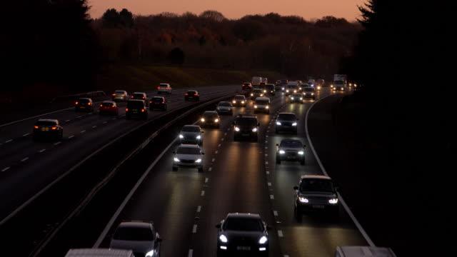 traffico autostradale al crepuscolo, auto con fari. - autostrada a corsie multiple video stock e b–roll