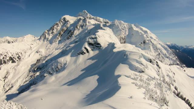 vídeos de stock e filmes b-roll de mount baker ski area aerial helicopter winter snowy flyover skiing snowboarding hiking riding on arm mt shuksan huge mtn top - encosta