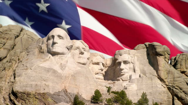 Mount Rushmore and American Flag The American flag waving behind Mount Rushmore National Memorial, South Dakota president stock videos & royalty-free footage