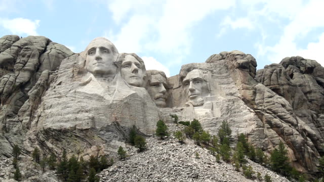 Mount Rushmore on a Sunny Day Mount Rushmore monument under sunny, summer sky.  White clouds drifting from left to right.  Cloud shadows occasionaly move across faces. president stock videos & royalty-free footage
