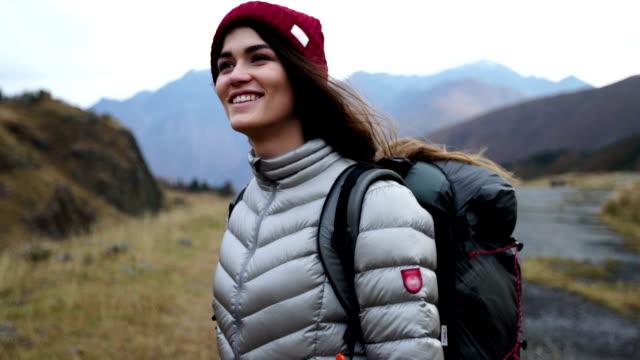 mountain adventure. young woman travelling - турист с рюкзаком стоковые видео и кадры b-roll
