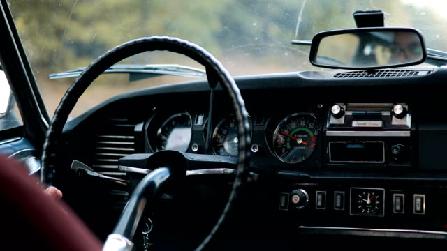 Mountain adventure.Young Man driving old fashioned car video