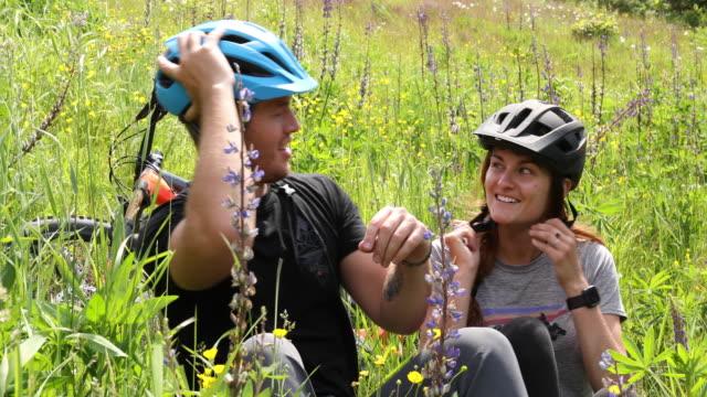 vídeos y material grabado en eventos de stock de pareja de bicicletas de montaña relajarse en prado de montaña - memorial day weekend