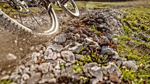 slo mo mountain bike pushing gravel into the air in sunshine - bike tire tracks video stock e b–roll