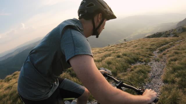 mountain bike rider cycling across rocky mountain landscape - andare in mountain bike video stock e b–roll
