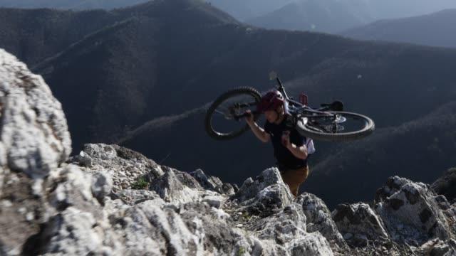 vidéos et rushes de vélo de montagne porte vélo vers le haut de crêteroc, jusqu'au sommet - évasion du réel