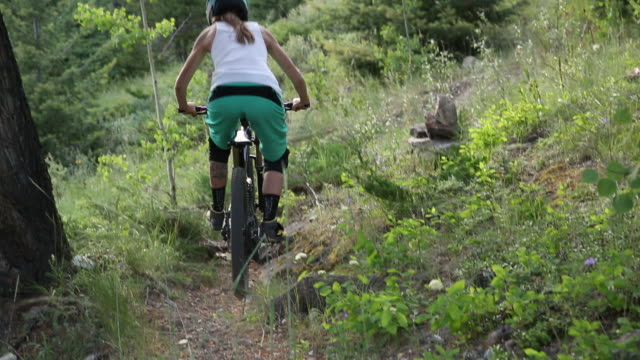 mountain biker descends steep trail - pantaloni capri video stock e b–roll