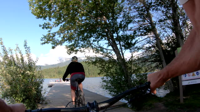 POV of mountain biker following female companion,on walkway