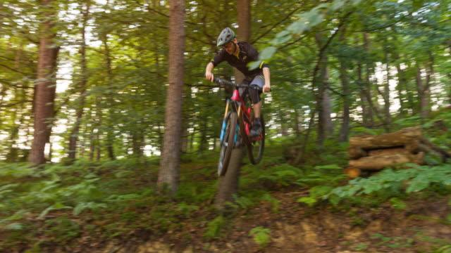 vídeos de stock, filmes e b-roll de mountain biker pulando de penhasco em trilha de terra, fazendo uma acrobacia - cavalgar