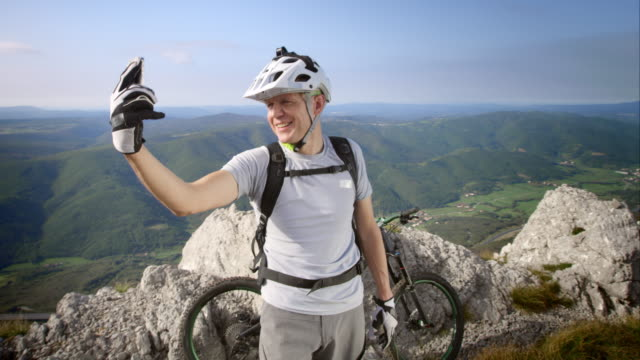 Mountain biker making video call as he reached the top video
