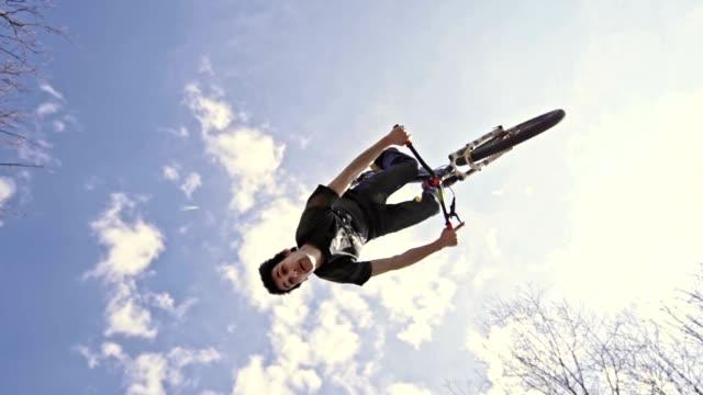 slo mo mountain biker performing backflip trick - трюк стоковые видео и кадры b-roll