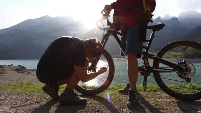 mountain biker performs bike repairs on trail, sunrise - bike tire tracks video stock e b–roll