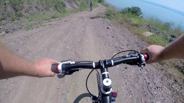 Mountain biker point of view cyclists riding bicycles on hill dirt track along wild sea shore video