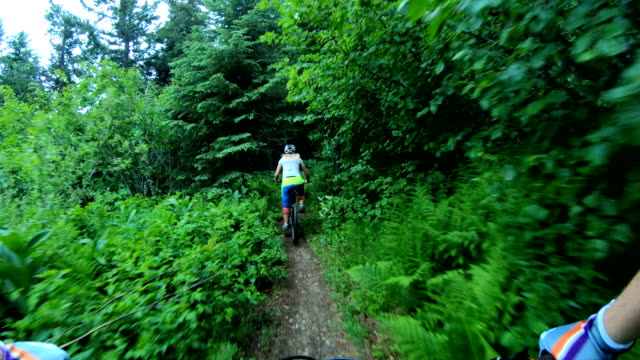 mountain biker point of view following young woman down rugged west coast trail - andare in mountain bike video stock e b–roll