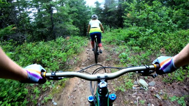 mountain biker point of view following young woman down rugged west coast trail - спортивное оборудование стоковые видео и кадры b-roll