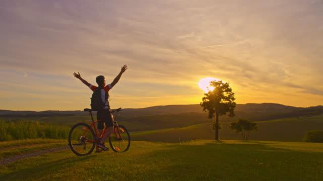 丘の上に空気を抜き slo mo マウンテン バイク - 後ろ姿点の映像素材/bロール