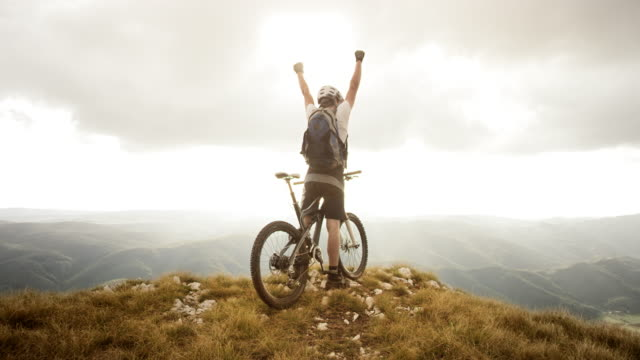 SLO MO mountain biker raising his hands at the top video