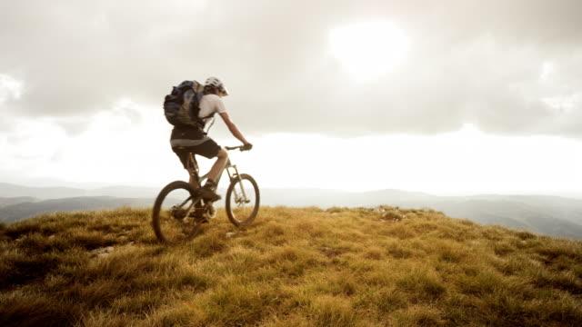 SLO MO mountain biker reaching the top and raising hands