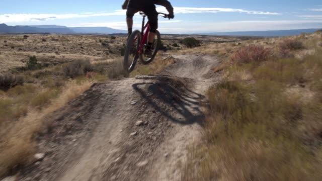 a mountain biker rides a desert trail on 18 road in fruita, colorado - bike tire tracks video stock e b–roll