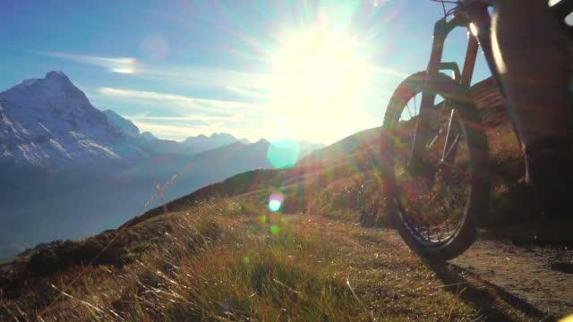 mountain biker rides along high mountain trail - andare in mountain bike video stock e b–roll