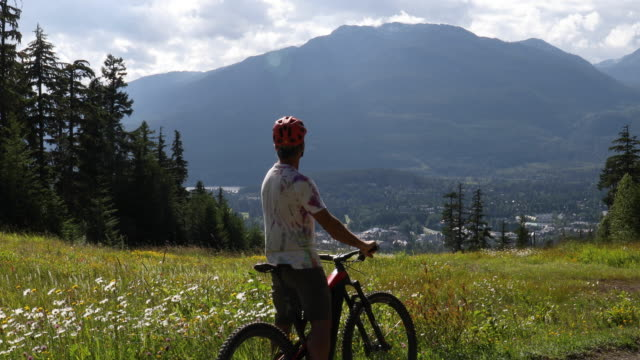 Mountain biker rides e-bike through alpine meadow He stops to enjoy view. Forest, village and mountains in distance lockdown viewpoint stock videos & royalty-free footage