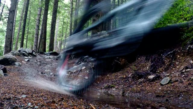 mountain biker rides through a puddle - andare in mountain bike video stock e b–roll
