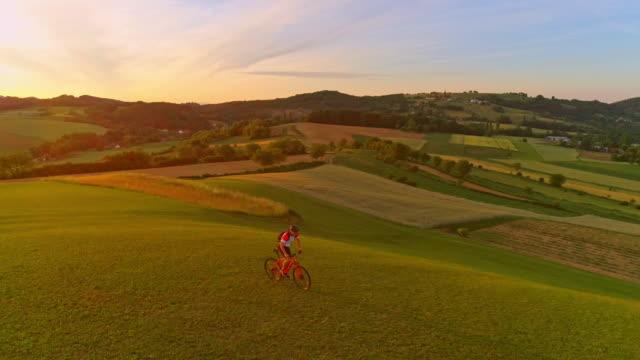 vídeos de stock, filmes e b-roll de motociclista aérea slo mo montanha, andar de bicicleta em um prado - persistência