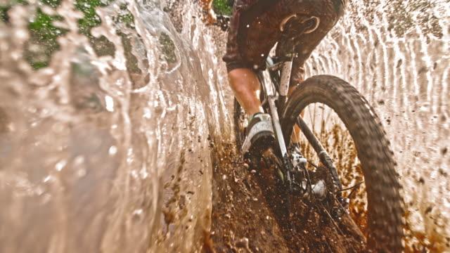 slo mo ts mountain biker riding through large muddy puddle - percorso per bicicletta video stock e b–roll