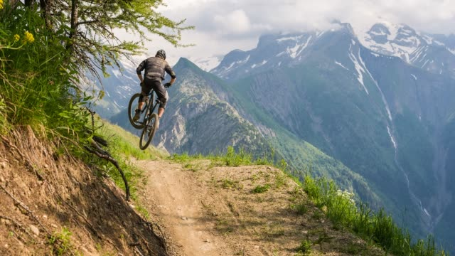 mountain biker speeding downhill, jumping on dirt trail, doing a stunt - andare in mountain bike video stock e b–roll